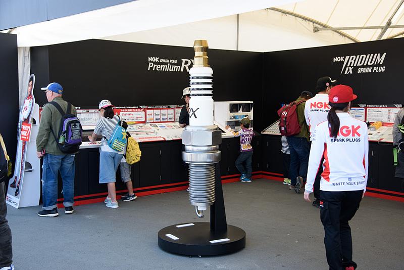 NGK スパークプラグ 鈴鹿2&4レースの冠スポンサーとなっている日本特殊陶業のブース。巨大な「プレミアムRXプラグ」がお出迎え