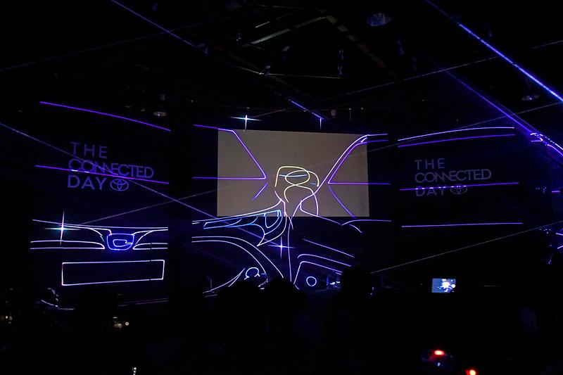 レーザーが暗くなったステージのパネルにクルマのシルエットを描き出す