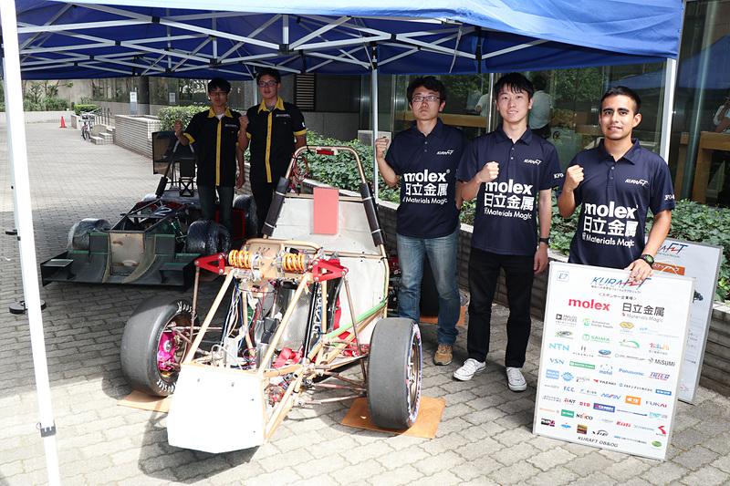 「第16回 全日本学生フォーミュラ大会」に参戦する芝浦工業大学 Formula Racing(左奥)と神奈川大学 学生フォーミュラプロジェクト(右手前)の参戦車両とチームメンバー