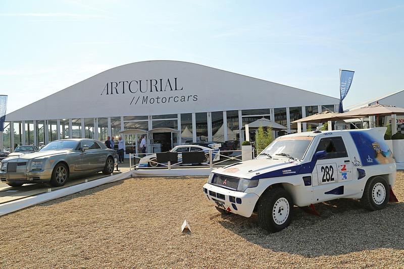 オークション会場前。オークションに出品されたパリ・ダカールラリーの三菱自動車工業「パジェロ」とランボルギーニのトラクター