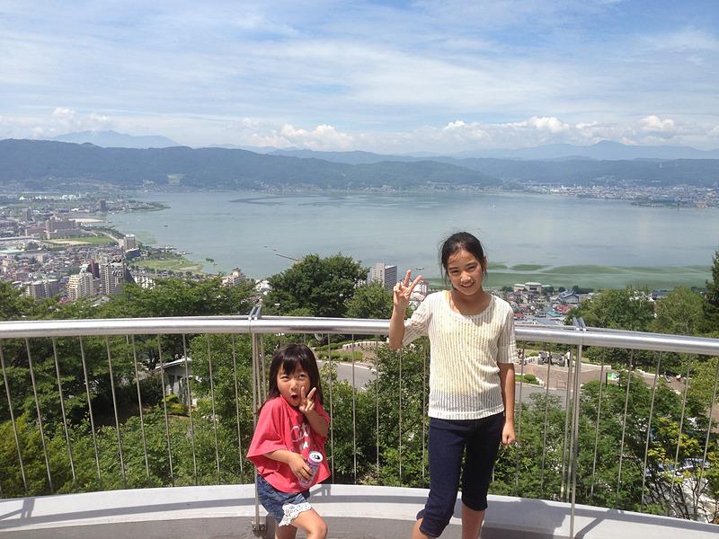"""諏訪湖やアルプスの山々が一望できる、とってもきれいな立石公園からの眺め。テンションが上がって""""ヘン顔""""していた幼い姪っ子も、今ではすっかり大きくなりました(笑)。ここは駐車場も無料、遊具もすべて無料なのが嬉しいところです"""