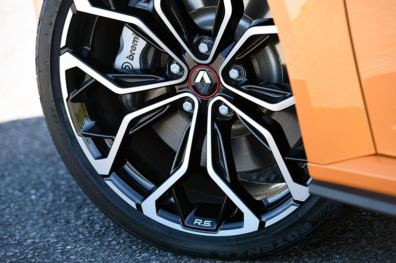 エクステリアではメガーヌ GTからフロントを60mm、リアを45mm広げたフェンダーが備わるとともに、F1スタイルのエアインテークブレードにワイドなエアインテークを組み込んだフロントバンパーを装備。スモールランプ、フォグランプ、ハイビームとしての役割を担うチェッカーフラッグ型の「R.S.ビジョン」も特徴の1つ。足まわりはカヤバ製で、タイヤはブリヂストン「POTENZA S001」(245/35 R19)