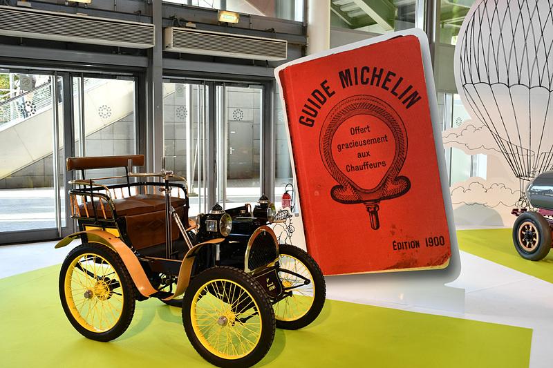 1898年製 ルノー 1号車の後ろには、1900年版のミシュランガイドをデザインした背景を用意。時代の雰囲気を感じやすいようにしていた