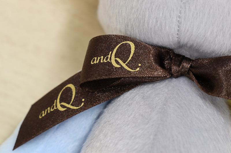 首のリボンと左足の裏に「and Q.」のロゴマークが入る