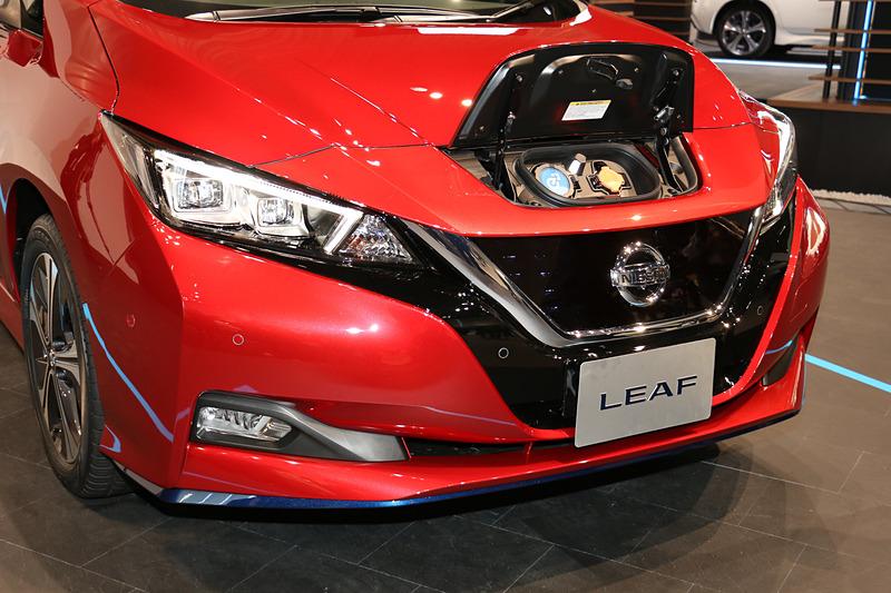 リーフ e+では車高が5mm高まり、走行用バッテリーの張り出しで最低地上高が15mm低下していることからフロントバンパー下側の形状を変更。ブルー塗装のリップスポイラーも追加された