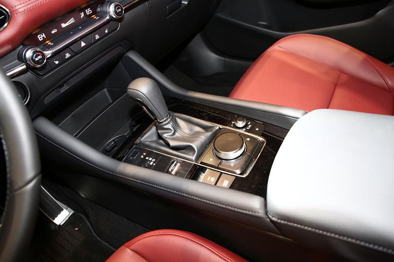 ハッチバック専用色となる「ポリメタルグレーメタリック」に塗装された新型Mazda3 CUSTOM STYLE(北米仕様ベース)。インテリアカラーはバーガンディで、マツダの新たな世界観を表現。エクステリアでも専用のエアロパーツを装備していて、ステージに飾られた「ソウルレッドクリスタルメタリック」や「マシーングレープレミアムメタリック」の新型Mazda3とは異なったテイストを醸している