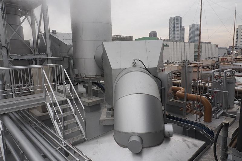 ガスエンジンは建物内にあるが、排出ガスは屋上に向け、騒音の低減などを図っている。48万3000ccのエンジンだけに消音装置も大きい。ふそうのディーゼルエンジンと同様に尿素による排出ガス浄化システムも備わっている。取材時は気温が低かったため湯気となっているが、特に匂いなどはなかった