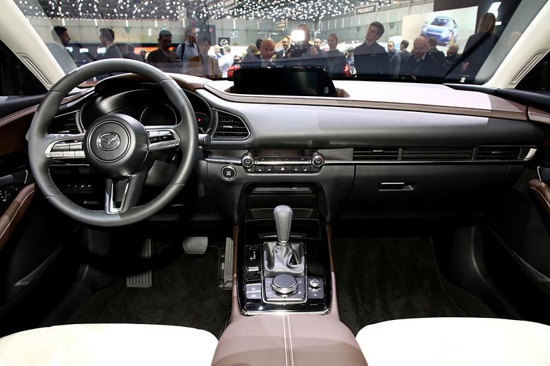 コクピットまわりの左右対称なデザインや、スイッチとエアコン吹き出し口の横基調は新型「Mazda3」と同様となる。CX-30の特徴は、助手席側からダッシュボード上部に回り込み、空間を包み込むようなデザイン。パッセンジャーカーとして居心地のよい室内を生み出すために施された、独自のインテリアとなる