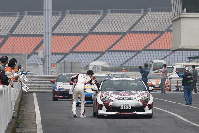 同チームであるプロクラスドライバーの佐々木雅弘選手からブリヂストンのフラッグをもらい、ピットロード凱旋
