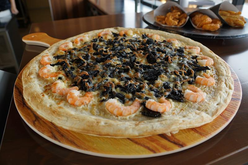 COURSE SIDE PIZZERIA -GRAN VIEW-ではさまざまな種類のピザが提供される。写真は鈴鹿サーキットのお土産として人気の「タイヤカスさきいか」とイカスミソースを使用した「タイヤカスブラック」(8分の1カットで提供される)