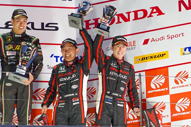 表彰台でトロフィを掲げる道上龍選手(中央)と大津弘樹選手(右)