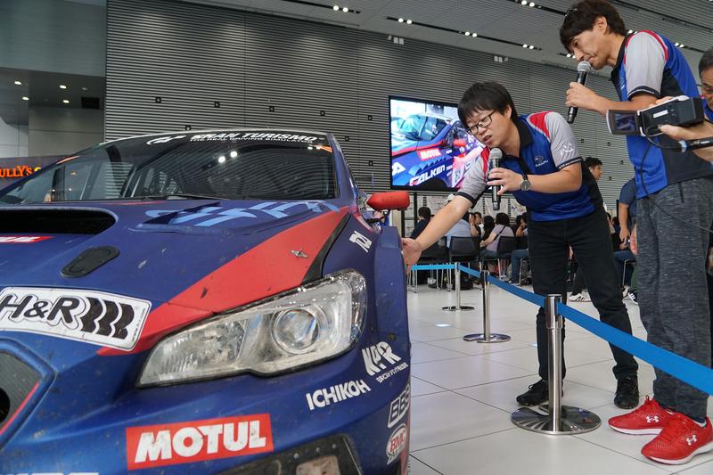 他のマシンと接触するトラブルが発生したときの気持ちなどを実車を前に説明する、STI 車両実験部 チーフエンジニアの宮沢竜太氏