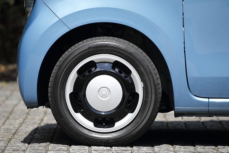 足下は14インチスチールホイール+フルホイールキャップ(2トーンカラー専用)にブリヂストン「エコピア EP150」(155/65R14)の組み合わせ。足まわりでは全車でフロントスタビライザーを採用したほか、ダンパーに対してスプリングをオフセットさせる構造を用いることで、タイヤが上下動した時にダンパーロッドに発生する曲げ方向の力を低減する「横力キャンセルスプリング」を採用