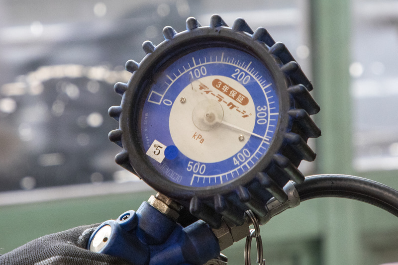 N-VANは貨物用タイヤなので空気圧は高め。指定空気圧ではフロントが2.8kgf/cm<sup>2</sup>でリアが3.8kgf/cm<sup>2</sup>となっている。点検に出す少し前、スタッドレスタイヤに履き替えた時に自前のエアゲージで合わせておいたのだが、ホンダカーズのサービスで使用するエアゲージでは約0.2kg/cm<sup>2</sup>ほど低く出た。筆者が使っているエアゲージは安価な輸入物で、購入してから1回も校正していないのでズレがあるようだ