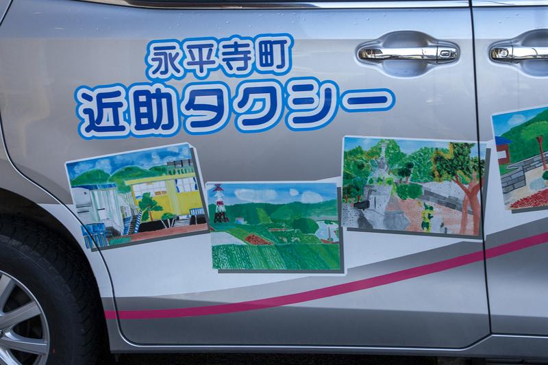 ボディ両サイドに描かれるイラストは、近助タクシーが運行する地区にある志比北小学校の子どもたちが描いたもの