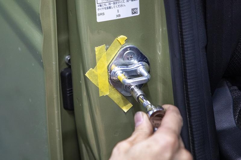 ストライカーを動かしてドアの位置を微調整。マスキングテープで元の位置をマーキングしてから取り付けネジを緩める