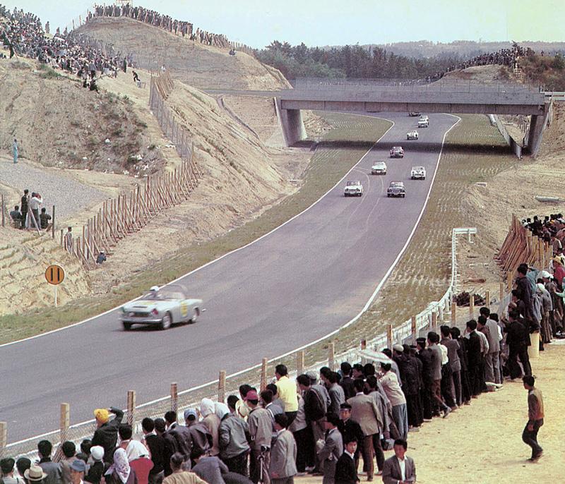 1963年、第1回日本グランプリ自動車レース、国内スポーツカーB IIクラス。ヘアピンのイン側に観客エリアがあり、立体交差の左上を見ると130Rの外側とデグナーのイン側の土手が高く観客エリアとなっている。デグナーのアウト側も切り立った崖でかなりの観客が見える