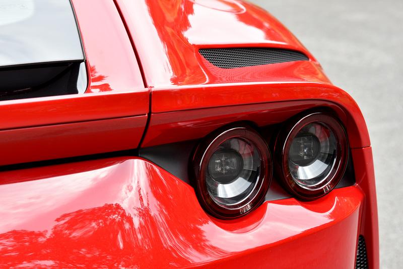 外観ではハイ・テールの2ボックススタイルが1969年の「365GTB4」を想起させ、フルLEDヘッドライトは隆起するフロントホイールアーチを含めてボンネットのエアインテークと一体でデザインすることでフロントの力強さを強調。リアまわりでは、フェラーリ伝統の4灯丸型テールランプが水平方向に広がるフォルムを強調し、スポイラーとキャビンを低く見せる視覚的効果によってワイド&ローを演出しているという。エキゾーストパイプはチタニウム製