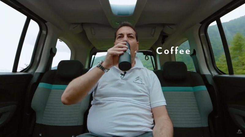 ベルランゴのリアシーリングボックスからタンブラーを取り出してコーヒーを飲むGroupe PSA Japan株式会社 代表取締役社長 アンジェロ・シモーネ氏