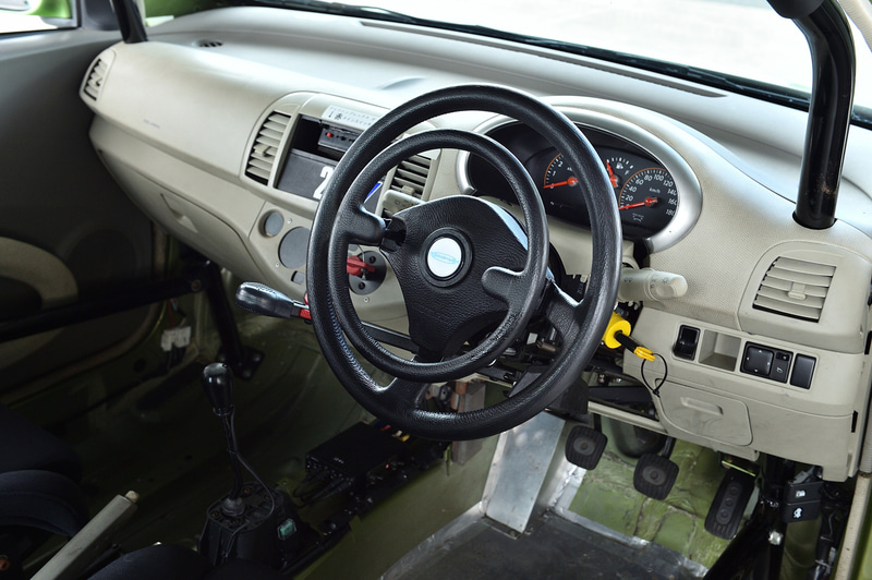 グイドシンプレックス製の手動運転装置。ハンドル左のコラムシフトのようなレバーを前に押すことでブレーキ、ハンドル中央のリングを押し込むことでアクセル