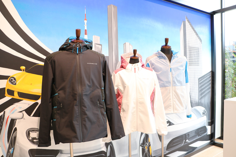 耐水圧3000mm、透湿性3000g/m<sup>2</sup>/24時間のジャケット。フード、ショルダー、背面、およびサイドパネルはパッド入り。胸に光を反射するポルシェロゴ入り。価格5万2580円
