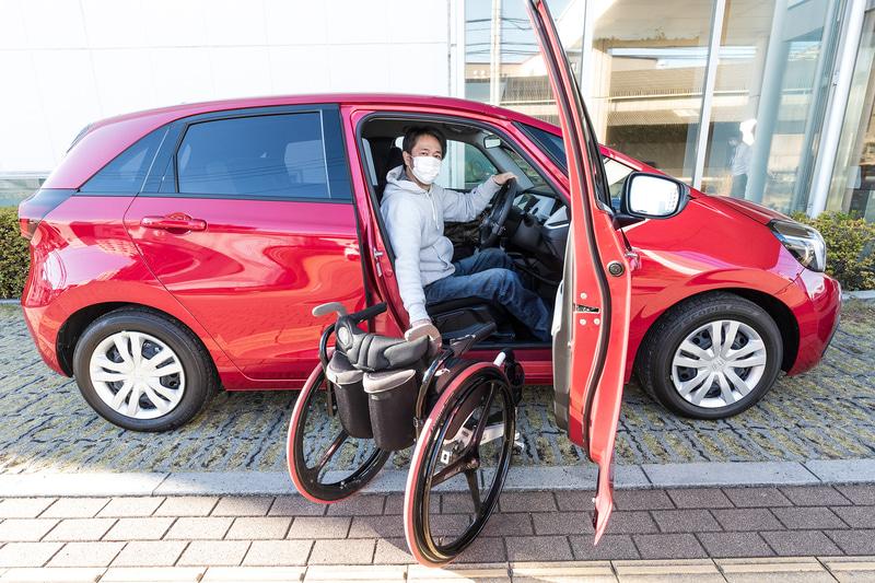 「フィット e:HEV BASIC Honda・テックマチックシステム手動運転補助装置 Dタイプ装着車」に乗り込む車椅子ユーザーの筆者