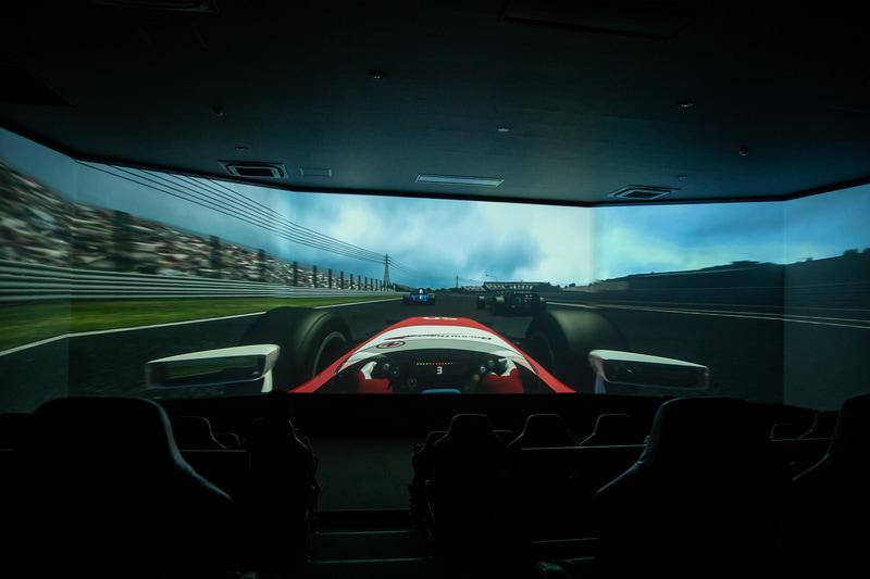 幅19mのワイドスクリーンの前に60席のバケットシートが並び、音と振動でレーシングドライバーが実際に見たり感じたりするスピード感や迫力を体験できる
