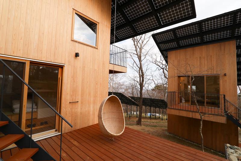 Looop Resort NASUの宿泊する個室棟は2棟あり、どちらも2階建てで上には太陽光パネルが載る。軒下が大きく、テラスも日陰になって過ごしやすい