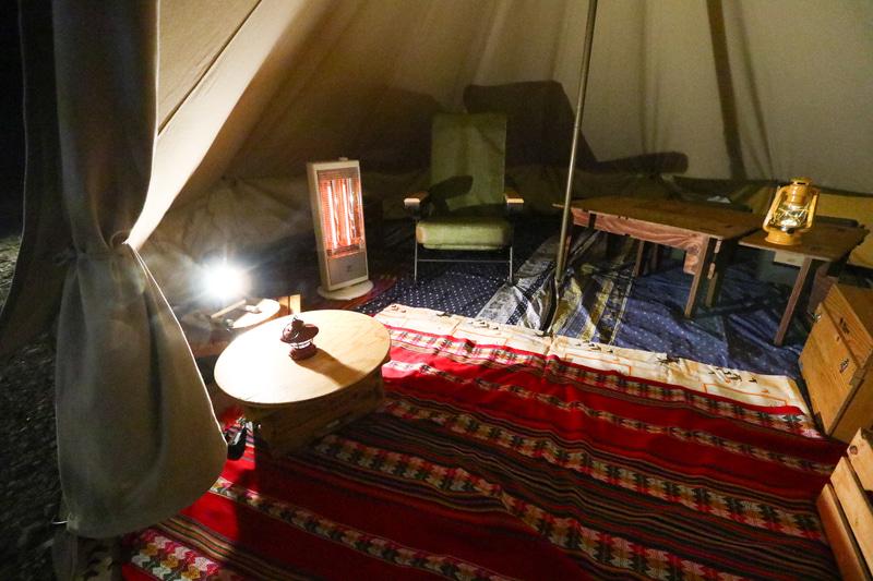 テント内の様子。1000Wの電気ストーブと電気マッサージチェアがあるほか、電気毛布なども用意している