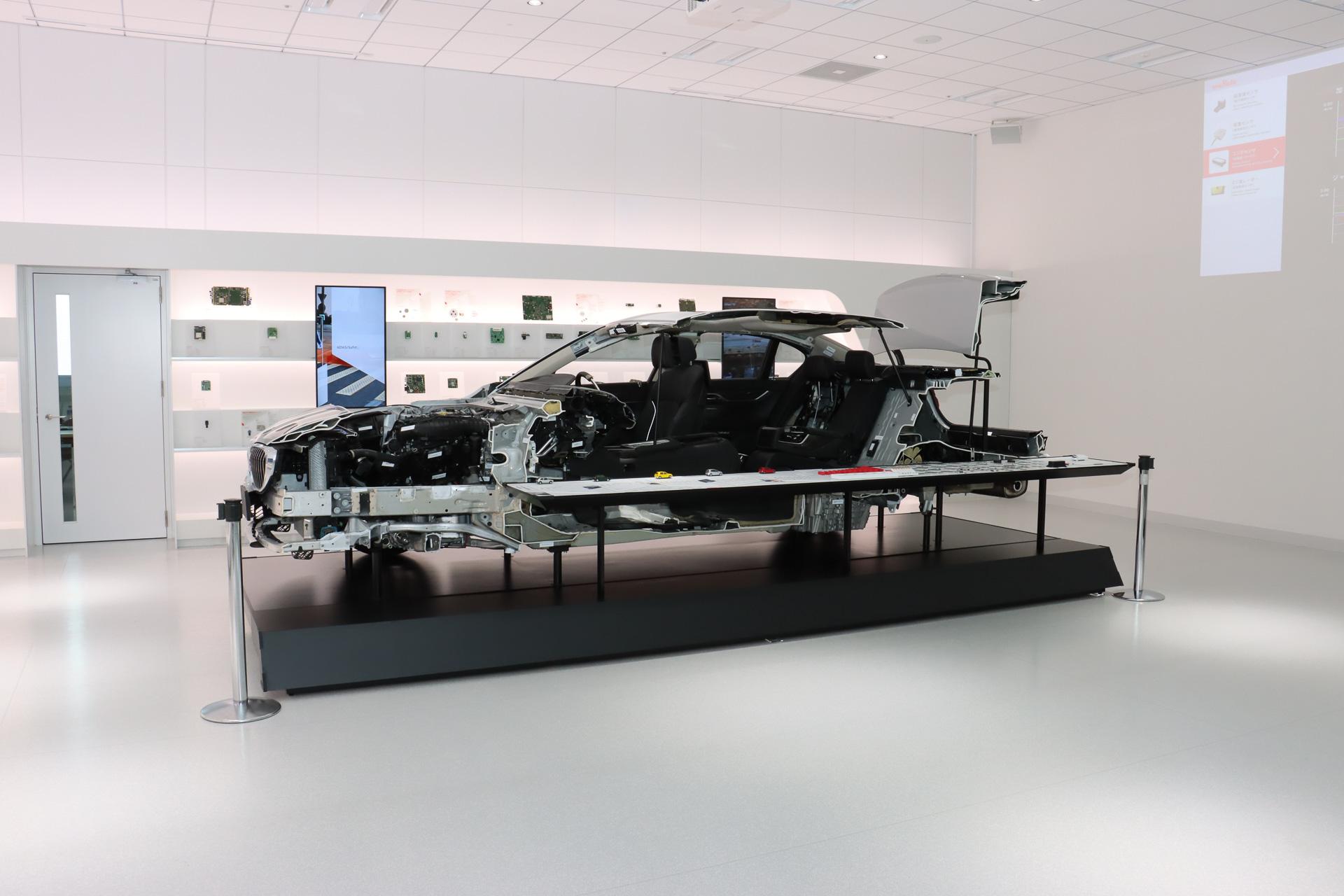 スペース中央に車両のカットモデルをシンボリックに置くことで、同社が自動車市場に本気で取り組んでいる姿勢を表現