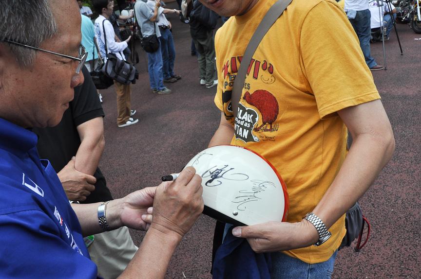 イベント参加者のヘルメットにサインをする高橋氏。このヘルメットのデザインも高橋国光レプリカになっていた。高橋氏のサインの横には長谷見氏のサインも