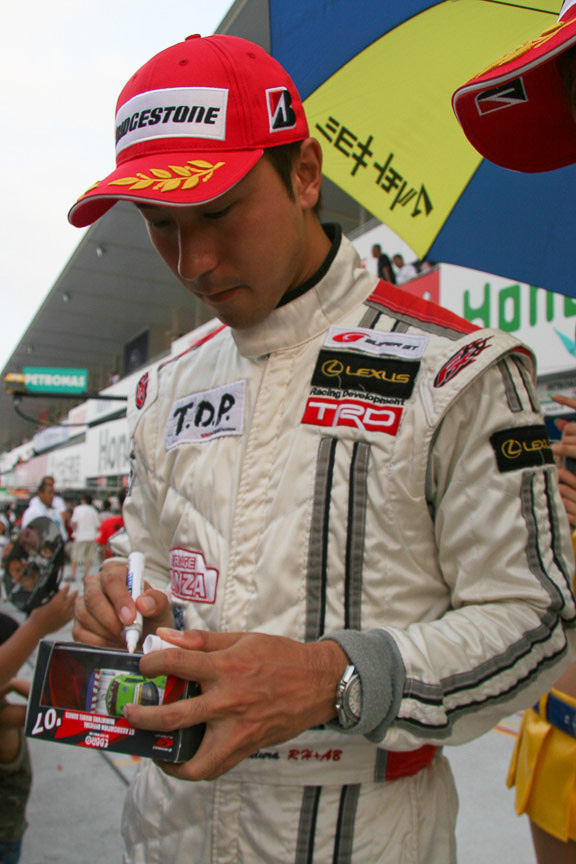 2007年のトイ・ストーリーレーシングのミニカーにサインする石浦選手と大嶋選手