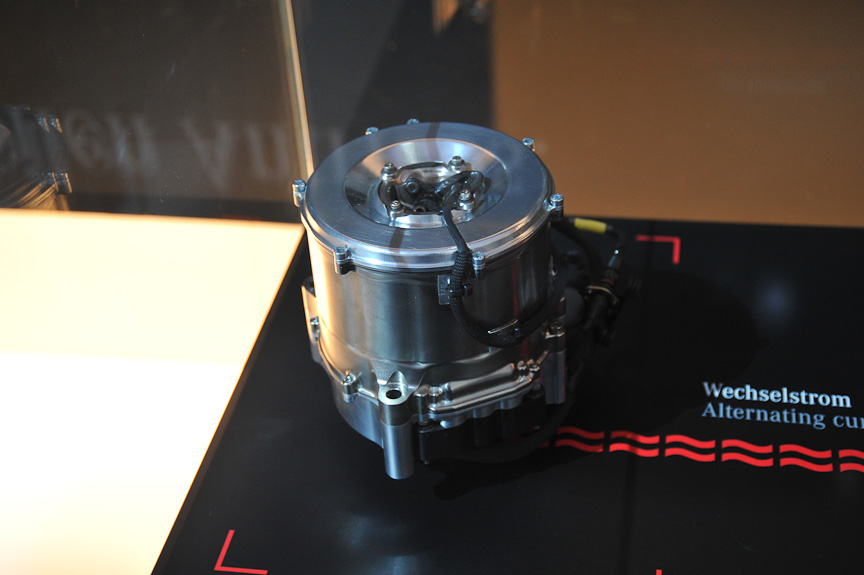 """会場にはさまざまな環境対応技術が展示されていたが、その中でもひときわ目を引いたのがF1用ハイブリッド、つまりKERS。マクラーレン・メルセデスに搭載されているもので、現在のF1用KERSではもっとも""""使える""""と言われている。一番大きなユニットが充電池"""