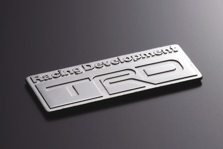 「TRDエンブレム(Bタイプ)」。材質に真鍮を使用し、ロジュームメッキ仕上げ。サイズは70×26mm(幅×高さ)。5460円