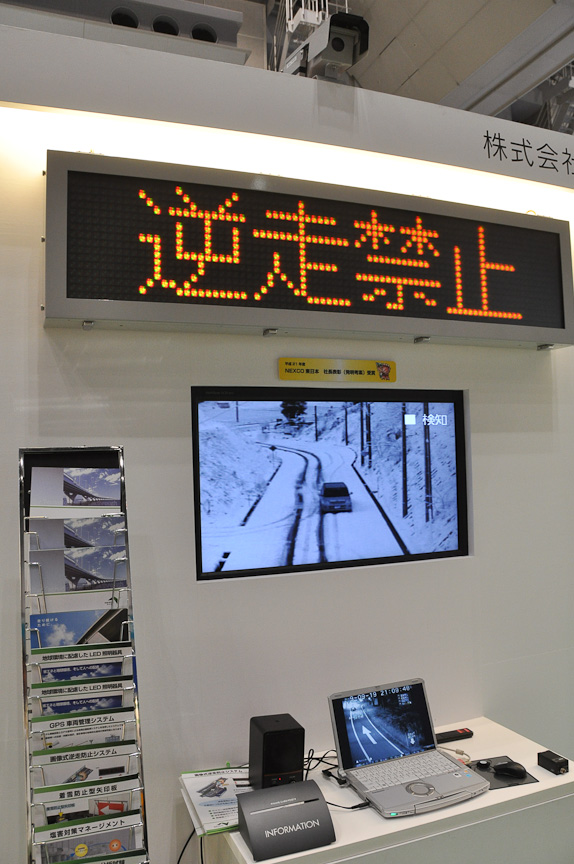 NEXCO東日本ブースに展示されていた「画像式逆走防止システム」。上部のカメラで撮影した動画を処理して逆走であることを認識し、電光掲示板で警告する。逆走による事故は社会問題となっているが、それをできるだけ防ぐことを目指したもの。担当者によると、故意の逆走を行った2輪車1例を除き、この警告によってそのほかの逆走は防げたと言う