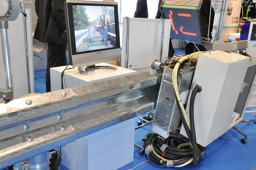 NEXCO西日本の「ガードレールリメイク工法」。ガードレール上を走行する特殊な自走機械を取り付け、ガードレールに付いたサビなどを落とす。自走機械では、ガーネット(ざくろ石)のブラスト材を噴出しサビを取る下地処理、アーク溶射による防食処理が行え、塗装処理を行えばガードレールをリメイクできる