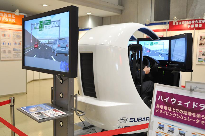 高速道路調査会が展示していたハイウェイドライビングシミュレータ。3面マルチモニターで、高速道路運転を体験できる。運転後は安全運転ドライビングのスコアが表示される