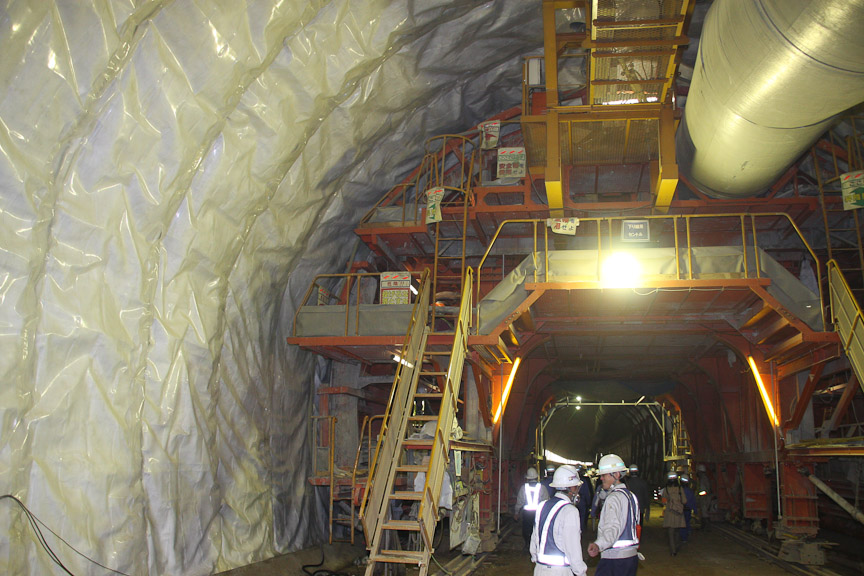 トンネルの入り口方向に向かって見たところ。オレンジ色の巨大な骨組みがスライドセントル。このスライドセントルと防水シートの間にコンクリートを流し込む