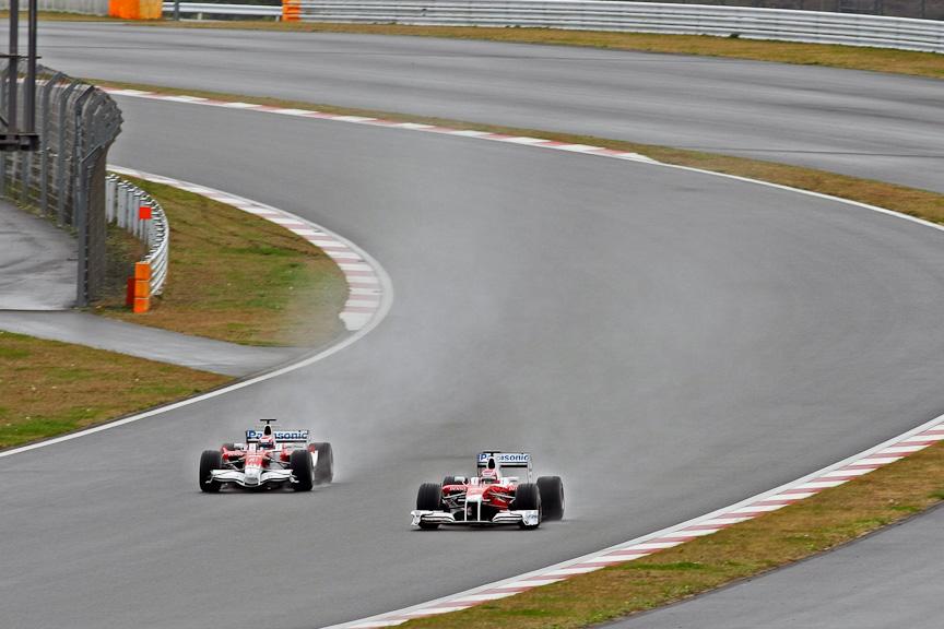 雨しぶきを上げながら2台のF1カーがランデブー