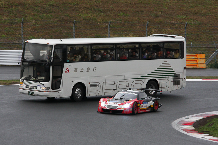 サーキットサファリで観光バスの横を抜いていくSUPER GTマシン。39号車「DUNLOP SARD SC430」