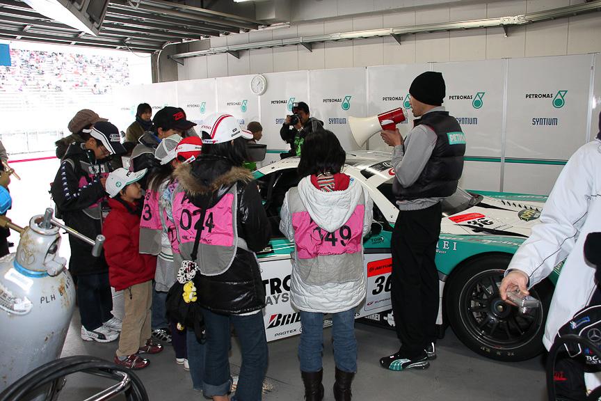「モータースポーツお仕事体験コーナー」の「キッズ記者体験」の様子。PETRONAS TOM'Sのピットで熱心に取材を行っていた