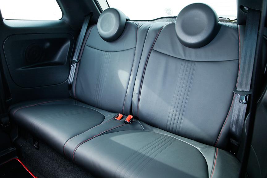 ブラック/レッドのツートーンカラーとなるヘッドレスト一体型スポーツレザーシートは、座面の高さ調整が可能。リアシートはブラック一色だが、赤いステッチが施される。円形のヘッドレストも洒落ている