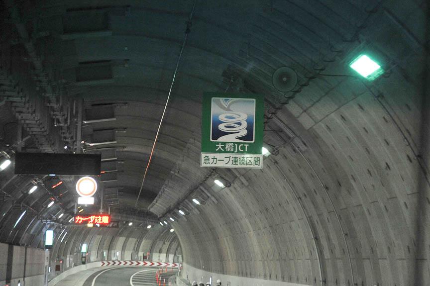 大橋JCTへの手前に2枚ある急カーブ連続区間の警告標識。大橋JCTの図案は漫画家の江川達也氏が原案を描いた