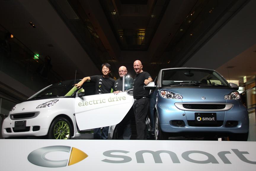 メルセデス・ベンツ日本 代表取締役社長兼最高経営役員(CEO) ニコラス・スピークス氏(右)と代表取締役副社長 上野金太郎氏(左)、スマート電気自動車 プロダクトマネジメント責任者 ピーター・ムース氏(中央)とスマート電気自動車(車両左)