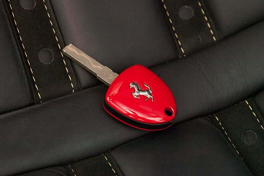 真っ赤なカバーのついたキーはリモコンでドアの施錠・解錠ができるほか、トランクのオープンスイッチも備える。裏面には跳ね馬がレイアウトされる
