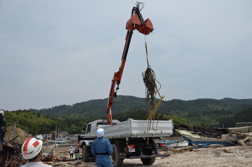 ゼトロスは鉄柱に絡まった漁網などを除去。ブームバケットについたフックに、漁網をまとめたロープを引っ掛けて引っ張り上げる。青い服に白いヘルメットのオペレーターは、ワイヤレスリモコンでブームバケットを操作している