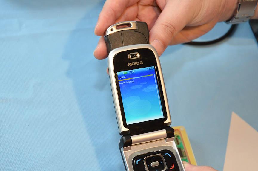携帯電話を鍵にかざし、鍵の中の情報を表示するデモ