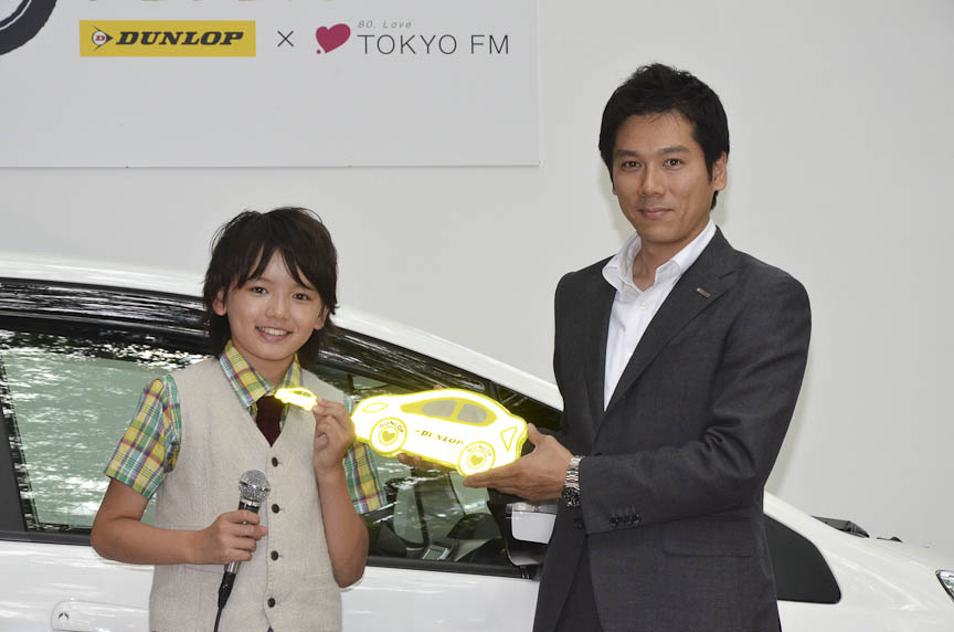 小学生に贈られるリフレクターを持つ濱田君