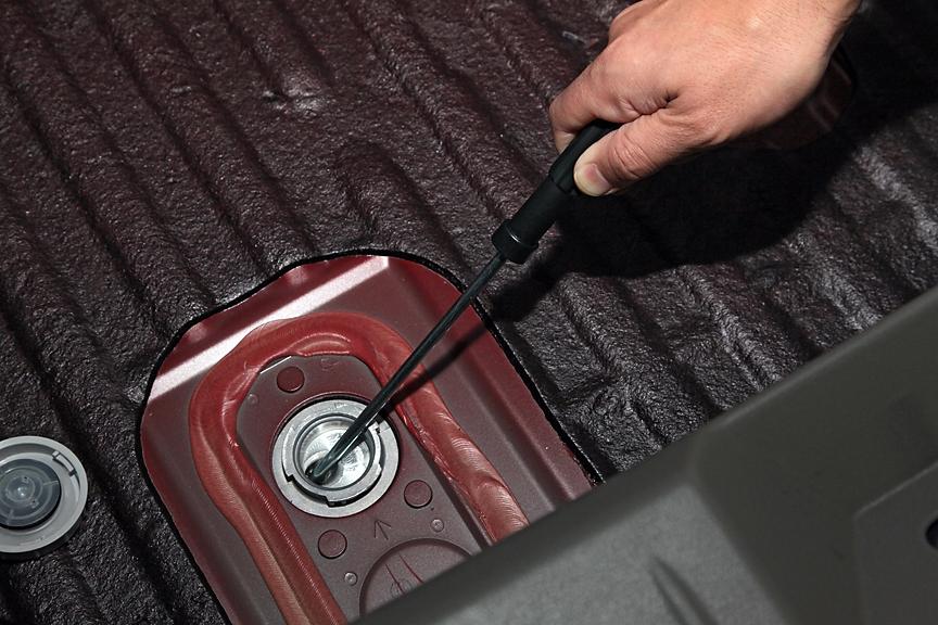 ラゲッジのカーペット下にある穴は電動パーキングブレーキのリリース用。バッテリー上がりなどで解除できないときに利用する
