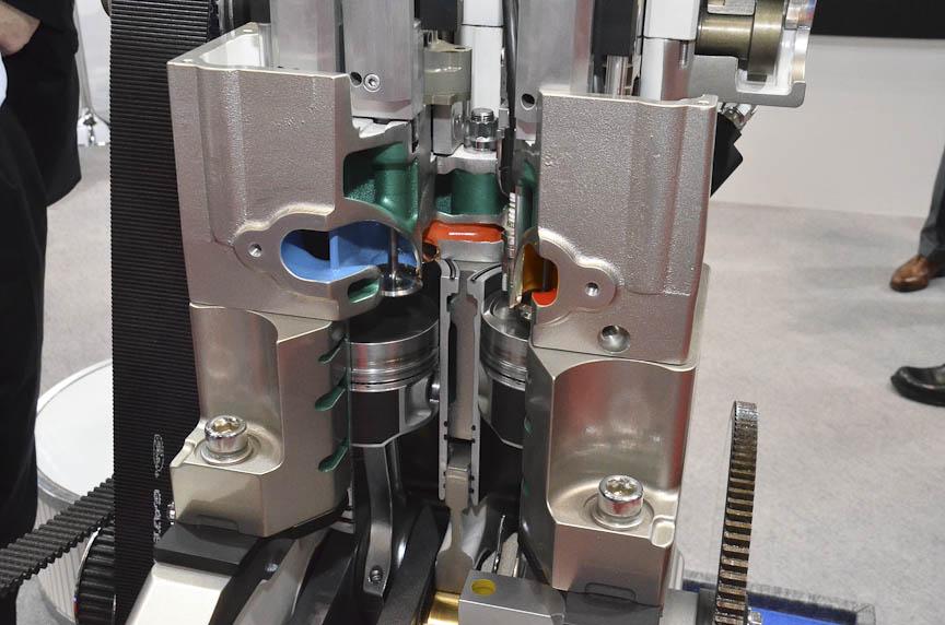 4ストロークエンジンだが、吸気と圧縮、燃焼と排気を別々のシリンダーに分け、4つの工程をクランクシャフト1回転で済ませるというアイデア。写真左のカットモデルは日本初公開で、左のシリンダーで吸気・圧縮された空気が、上部の緑色の通路を通って右のシリンダーに行き、燃焼・排気される